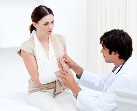 Young male doctor examining the female patient by taking her arms Stock Photo - 10109066