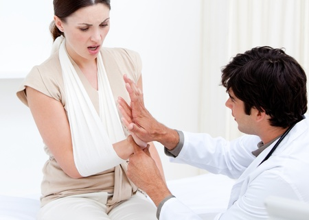 Professional male doctor examining the female patient by taking her arms Stock Photo - 10108406
