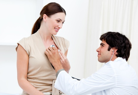 Male doctor examining  a smiling female patient with his stethoscope