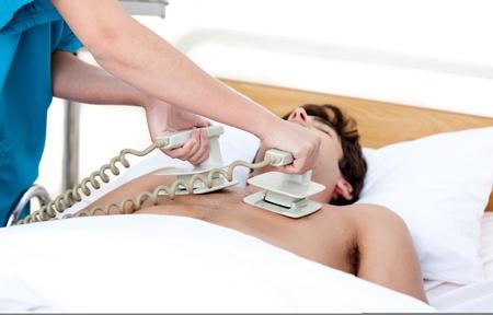 Doktor mit dem Defibrillator zu einem inconscious Patienten im Krankenhaus zu reanimieren