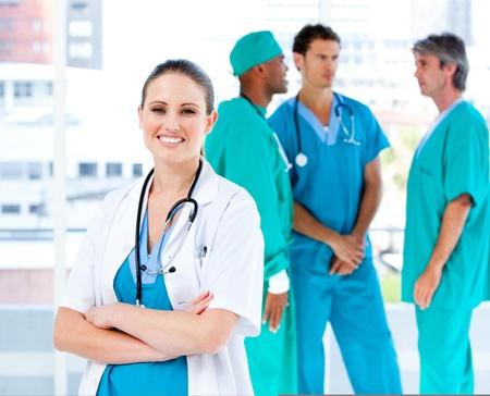 personal medico: Radiante mujer m�dico mirando a la c�mara mientras sus compa�eros m�dicos hablando juntos