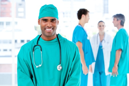 Afro male doctor looking at the camera while his medical partners talking together photo