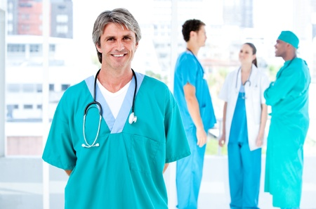 teaming: Joyful male doctor looking at the camera while his medical partners talking together