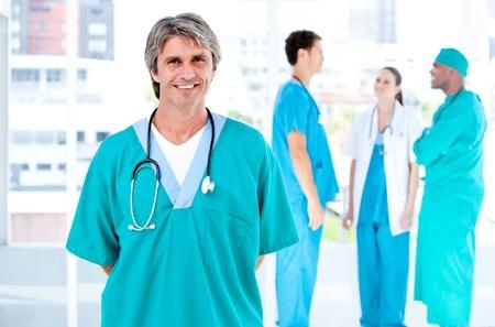 personal medico: M�dico alegre hombre mirando a la c�mara mientras que sus compa�eros m�dicos hablando juntos