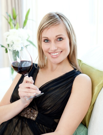 Beautiful woman drining red wine sitting on a sofa photo