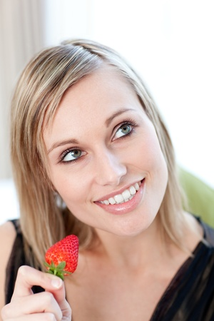 Bright woman eating a strawberry  photo
