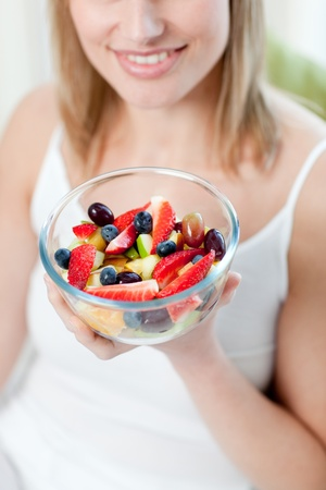 Attractive woman eating a fruit salad photo