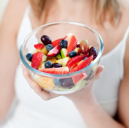Close-up of a caucasian woman eating a fruit salad  photo