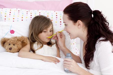 in syrup: Niña en la cama tomando jarabe
