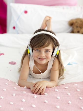 Little girl listening to the music in bed photo