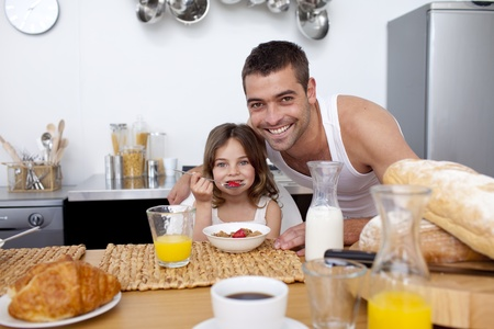 Daughter eating cereals and fruit in kitchen photo