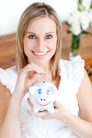 Jolly woman saving money in a piggy-bank  Stock Photo - 10128911
