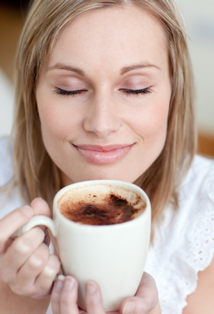 Delighted woman drinking a coffee photo