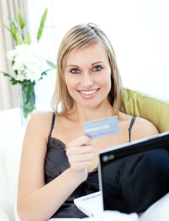 Joyful blond woman shopping on-line sitting on a sofa photo