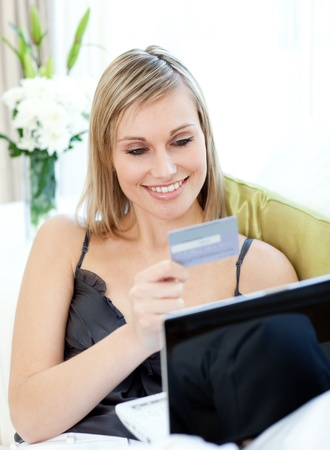 Attractive blond woman shopping on-line sitting on a sofa photo