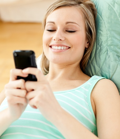 Smiling young woman sending a text lying on a sofa photo