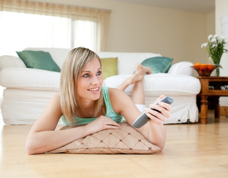 Beautiful blond woman watching TV lying on the floor Stock Photo - 10114961