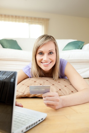 Happy woman shopping on-line lying on the floor photo