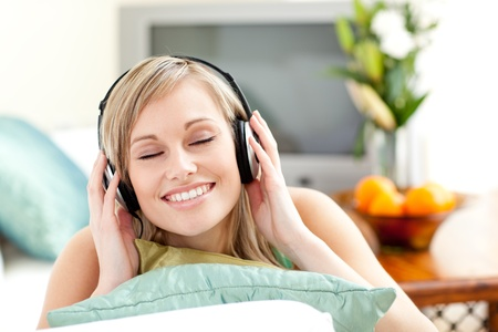 delighted: Delighted young woman listening music lying on a sofa