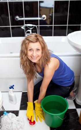 femme nettoyage: Positive jeune femme �tage de salle de bains de nettoyage