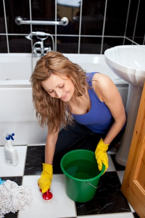 Smiling young woman cleaning bathrooms floor photo