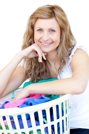 Happy woman doing laundry against a white background photo