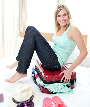 Attractive woman trying to close her suitcase photo
