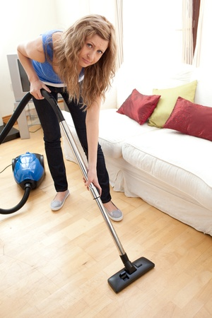 bored woman: Portrait of a bored woman vacuuming