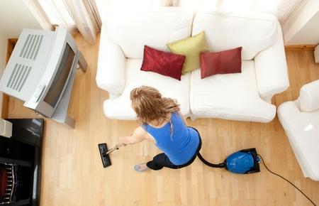 High angle of a blond woman vacuuming photo