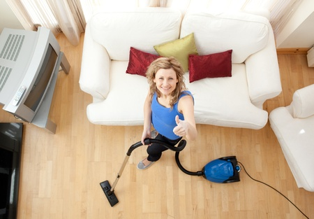 High angle of a cheerful woman vacuuming  photo