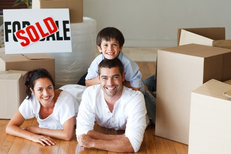 Happy parents and son lying on the floor after buying house photo