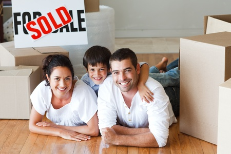 Happy family lying on the floor after buying house with boxes photo