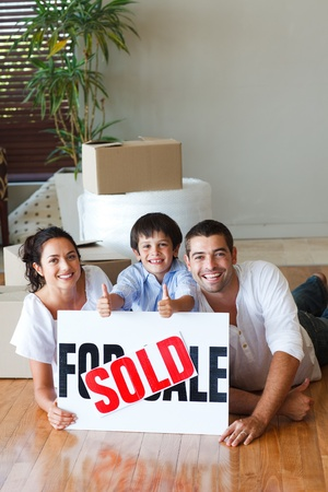 Family on the floor with boxes after buying house photo