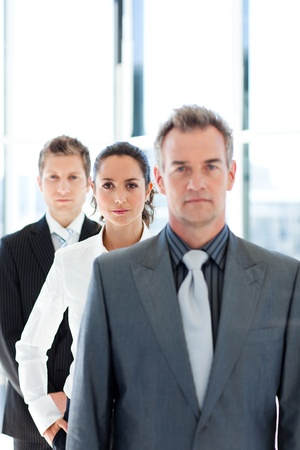 Confident businesswoman in focus with her team photo