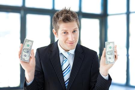 conserving: Businessman holding dollars