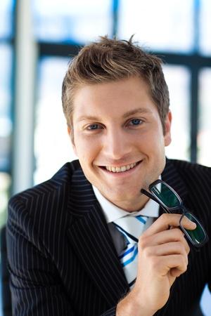 Smiling businessman holding glasses photo
