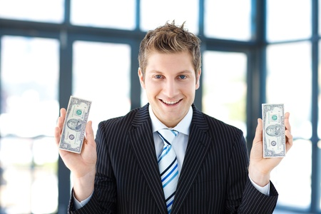 thousands: Smiling businessman holding dollars