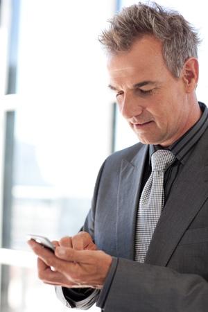 Mature businessman sending a text photo