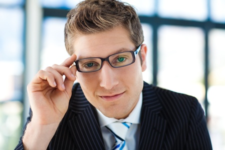 Businessman looking to the camera with glasses photo