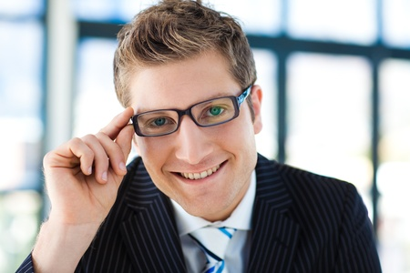 Businessman looking to the camera wearing glasses photo