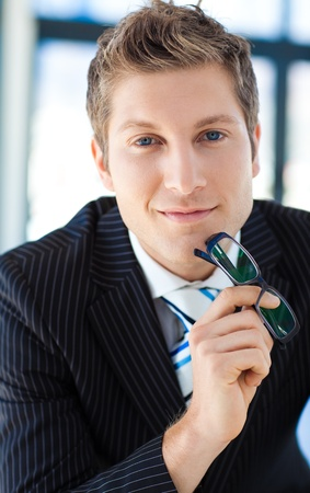 Businessman looking to the camera holding glasses photo