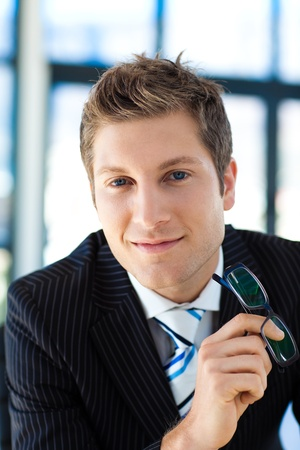 Attractive businessman smiling at the camera holding glasses photo