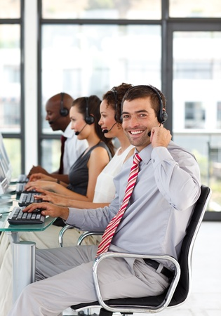Young businessman in a call center smiling at the camera Stock Photo - 10128680