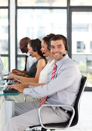 Friendly businessman working in a call center photo