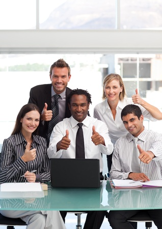 Multi-ethnic businessteam with thumbs up smiling at the camera photo