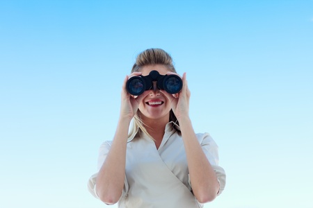 attentiveness: Smiling businesswoman looking through binoculars Stock Photo