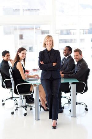 reunion de trabajo: Equipo de negocios sonriendo a la c�mara en una reuni�n Foto de archivo