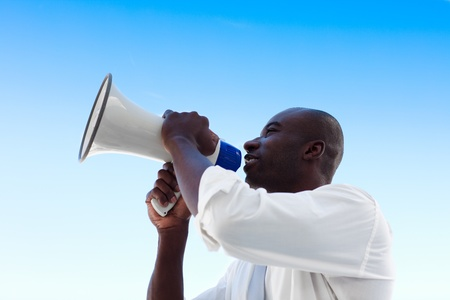 Angry African businessman shouting in a megaphone photo