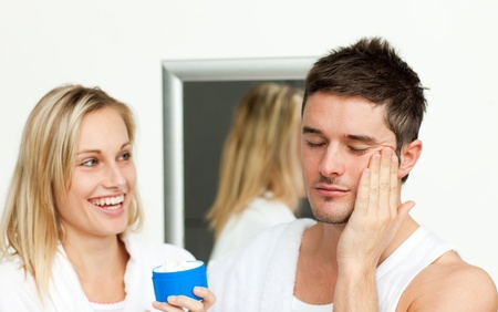 Man putting cream on his face with her wife photo