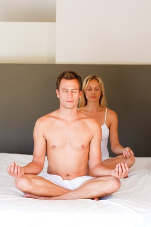 Couple doing exercises on bed with copy-space photo